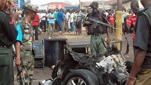 Security personnel inspect the mangled remains of a bomb-laden car that exploded in the northern Nigerian city of Kaduna on 8 April 2012