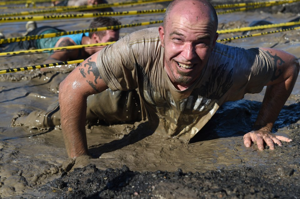 Man in mud smiling via Buckley Air Force Base - labeled for reuse on Google Images