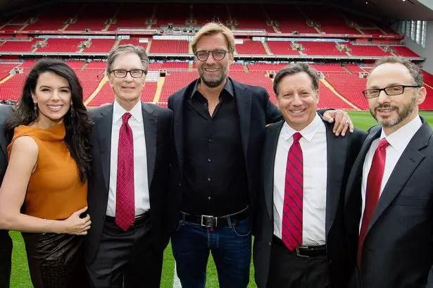 Jurgen Klopp posant sur le pelouse d'Anfield avec les dirigeants du Fenway Sport Group. (Source : liverpoolfc.com)