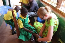 A newly sponsored child fitting her new full uniform - school bag, uniform, socks, and shoes