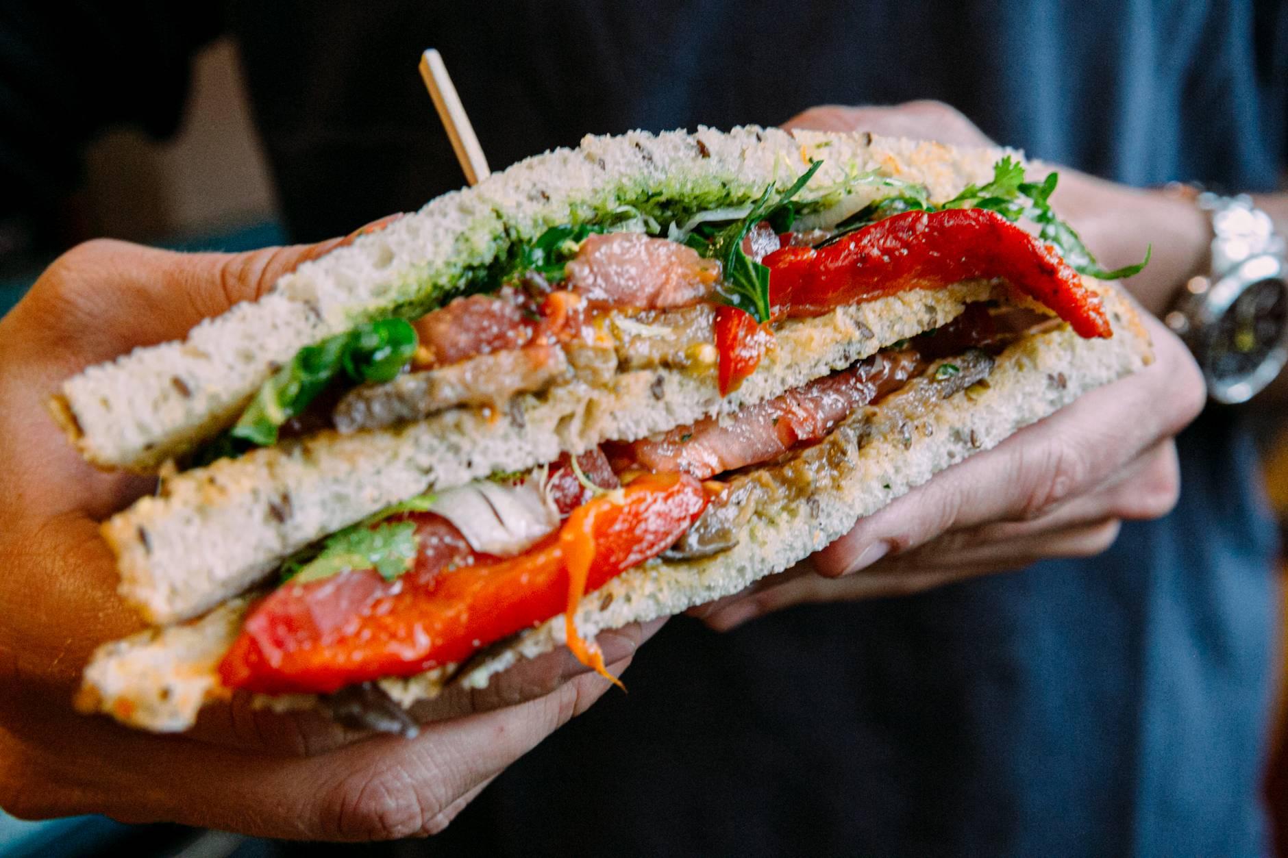 crop unrecognizable man showing appetizing fish sandwich