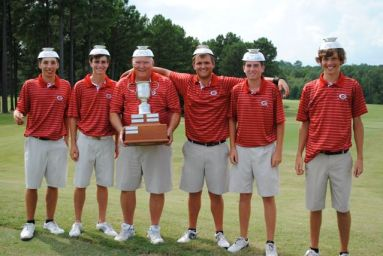 Golf team stands with trophy and bowls on their heads.