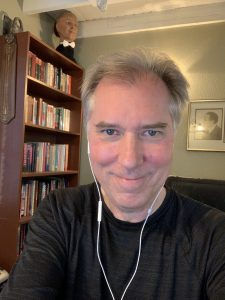 A selfie of John Cox in front of a bookshelf with a houdini prop of a human head in the background.