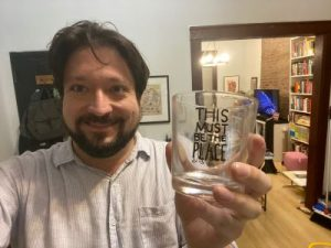 Dan McCoy in his apartment holding a Talking Heads glass.