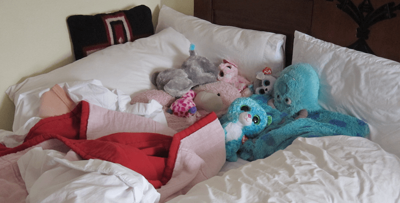 hotel bed covered in stuffed animals