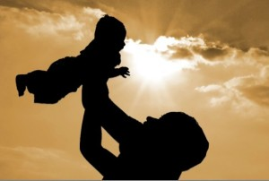 man holding up baby, against golden sunset