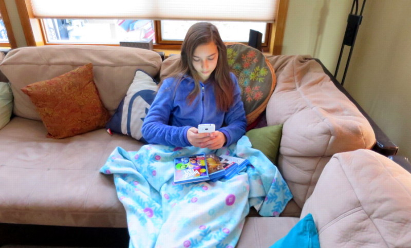 tween using smartphone / cellphone with dvd boxes on lap