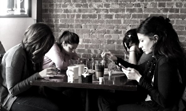 women using smartphones at restaurant table