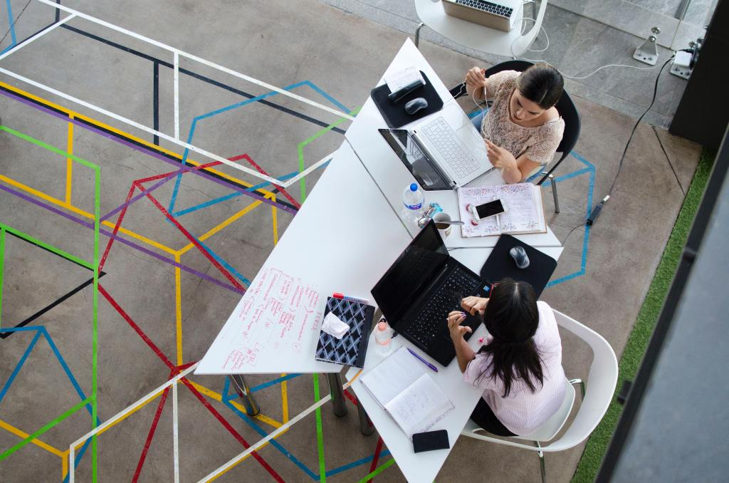 two marketers meet at a geometric table with their computers and smartphones to plan a digital transformation