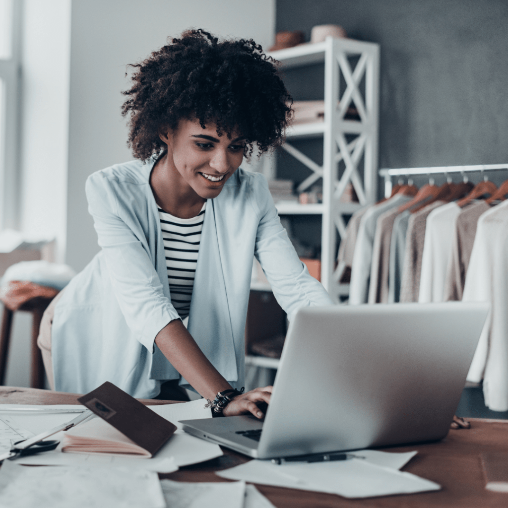 All filtered under muted neutral/pastel coloring, a Black woman dressed business-casual leans over her silver laptop on a desk sprawled with papers. Behind her, the room appears to be a design studio or boutique.