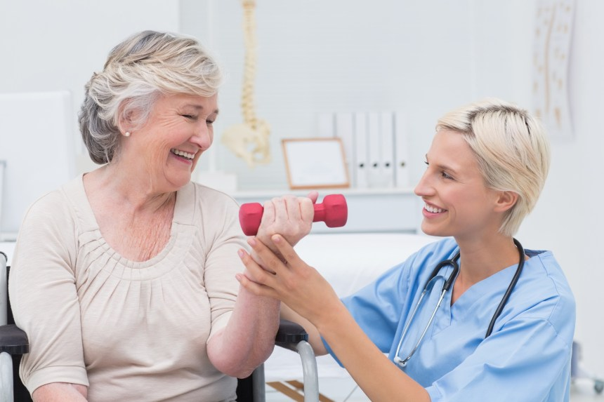 Nurse assisting senior patient in lifting dumbbell