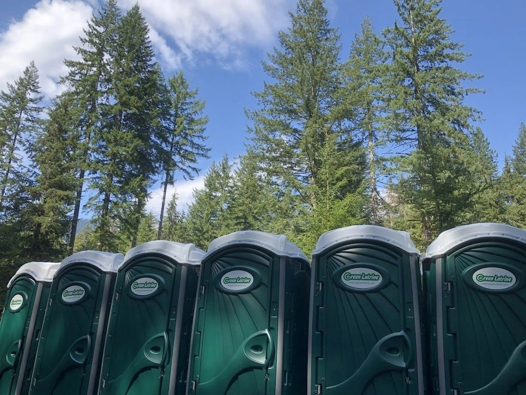 a Line of green Latrines with pine trees looming in the background