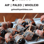 A bunch of bacon wrapped prunes on a white dish