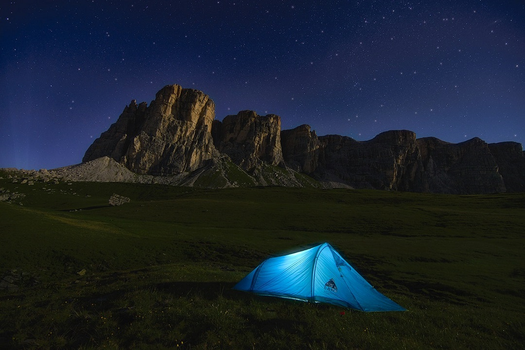 A bright blue tent on alpine grassland, against rocky towers and a deep blue starry sky