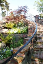 Gracefully curving brick staircase leading from the riverbank up to the Front Street garden entance