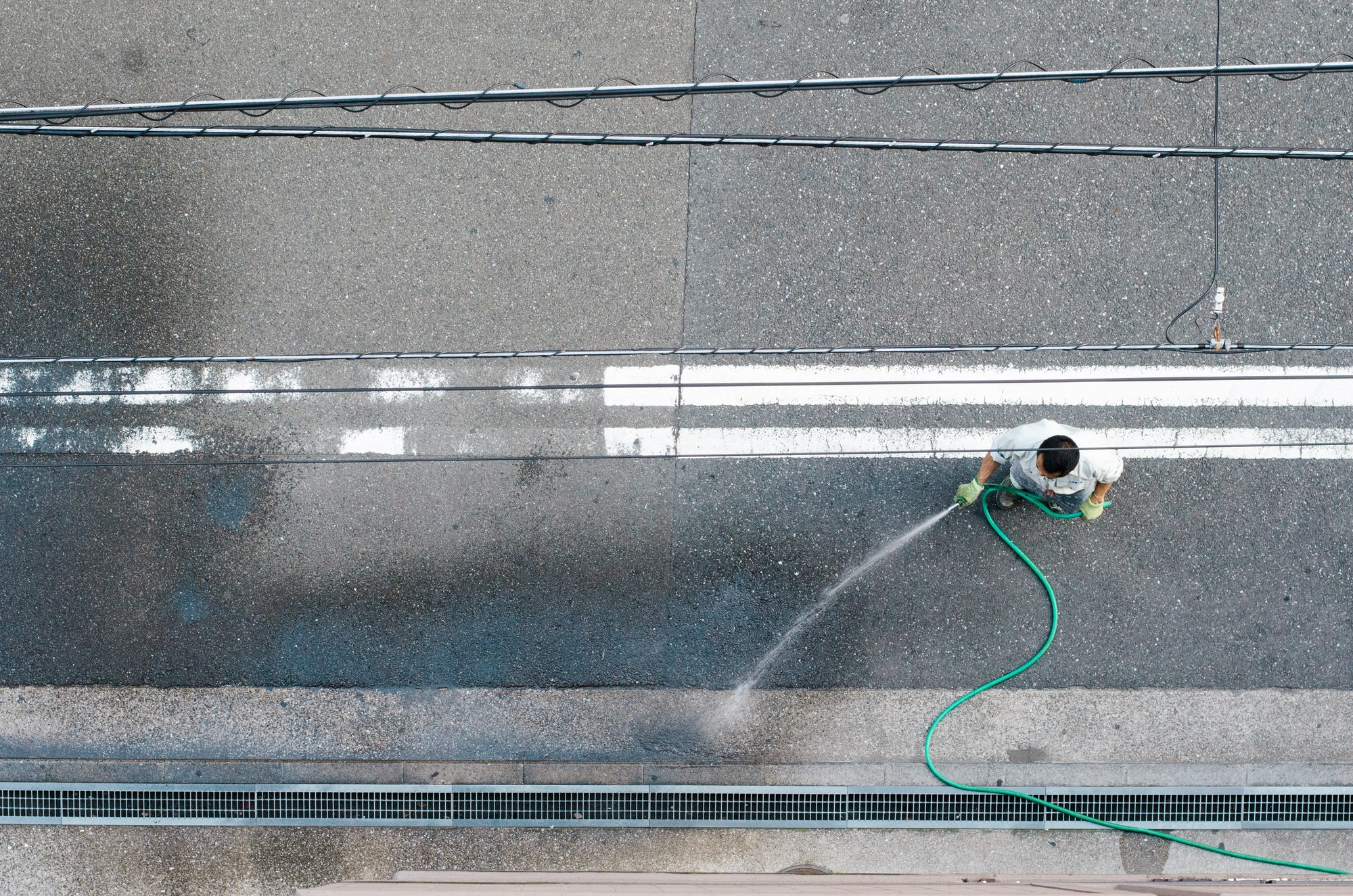 A maintenance worker cleaning the street outside an apartment building with a hose.