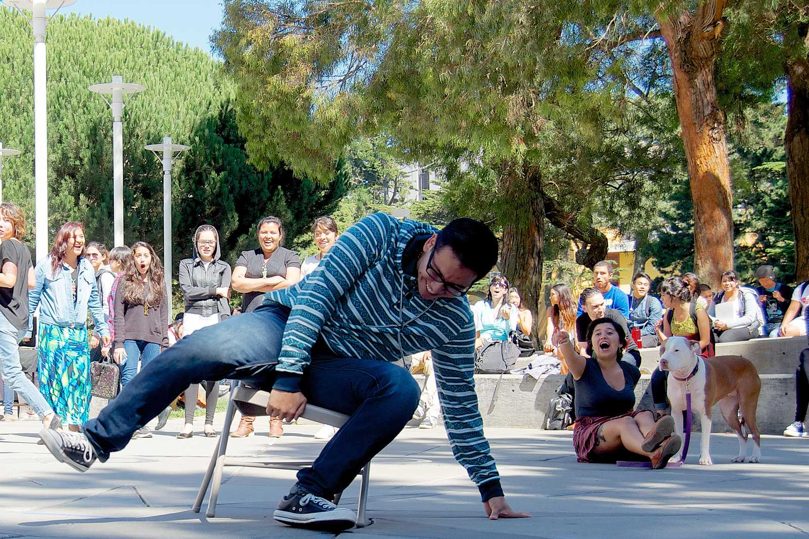 Javier Morelos Garza grabs the final seat during musical chairs at the La Raza Student Organization's festival in Malcolm X Plaza Sept 18, 2013. Photo by Kate O'Neal / Xpress