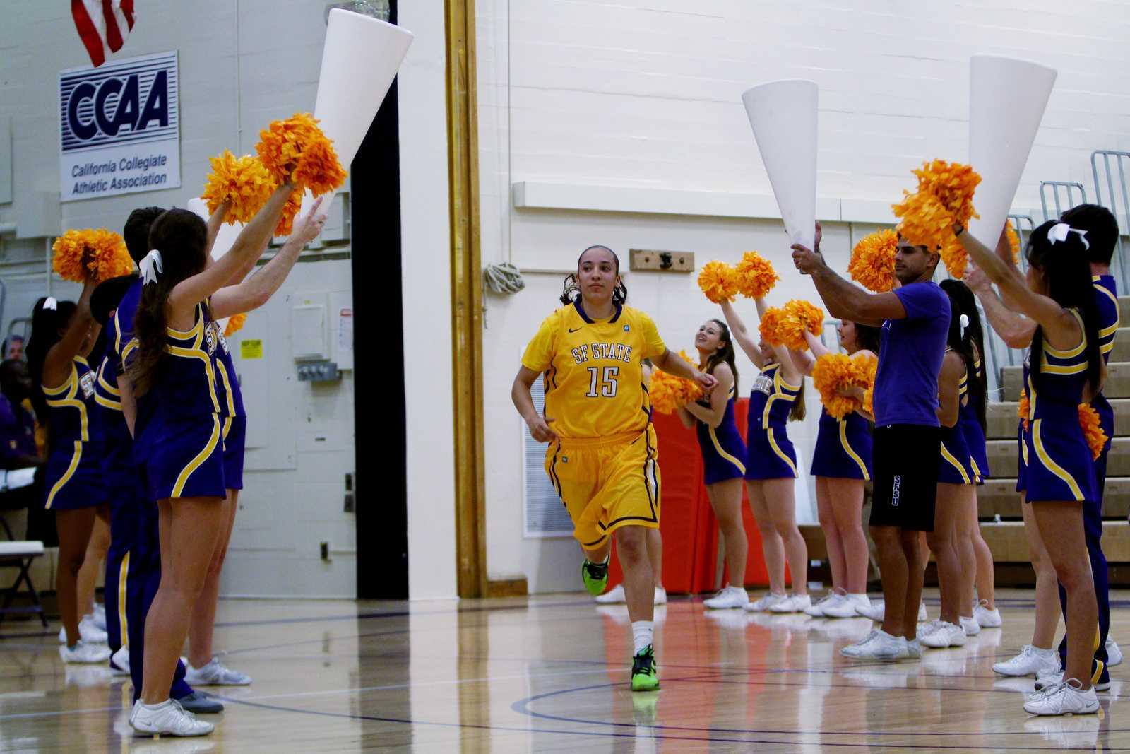 Kristian Juarez(15) runs between SF State's Cheer Team after being introduced at Gator Madness in SF State's Main Gymnasium, on Friday, Oct. 18. Gator Madness gave students the chance to meet athletes from the wrestling team, and the men's and women's basketball teams. Photo by Gavin McIntyre / Xpress