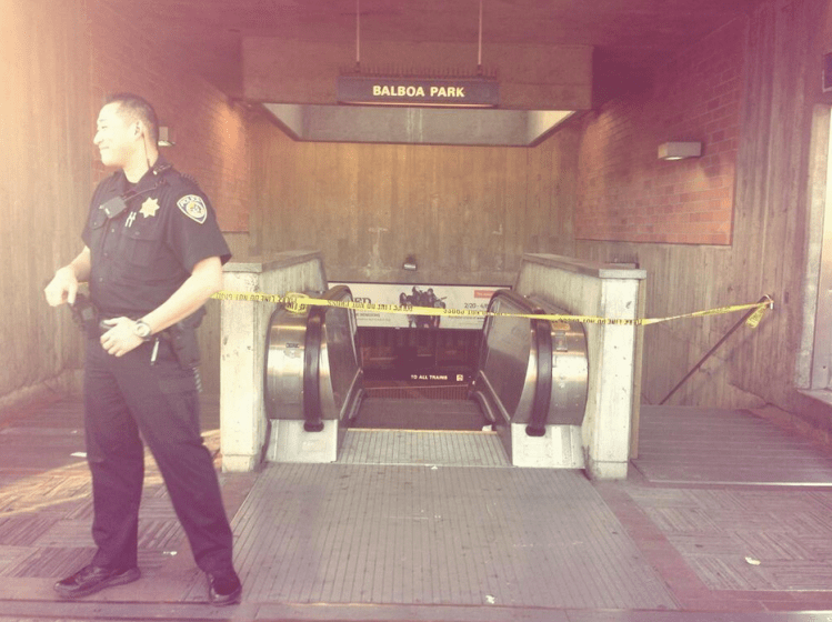 Police Officer S. Jung stands in front of a Balboa BART entrance that is blocked due to a possibly fatal accident on the tracks.