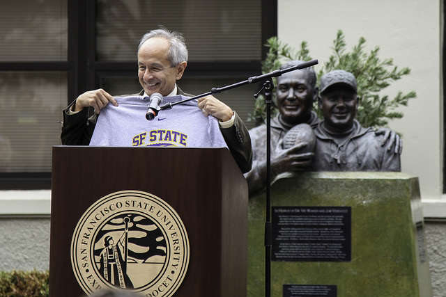 SF State president Leslie E. Wong holds up one of the new athletic t-shirts in Don Nasser Family Plaza during the reopening ceremony of the newly remodeled gymnasium on Thursday, Sept. 11, 2014. Frank Ladra / Xpress.