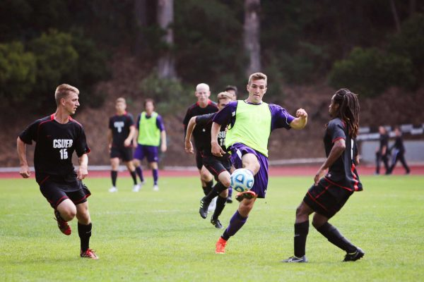 SF State Gator forward Cameron DeJong, # 16, volleys the ball out of the air away from advancing Cal State East Bay players, Kellen Crow, #15, and Arthur Ethel, #3, at Cox Stadium on Sunday, Sept. 28, 2014. Sara Gobets / Xpress.