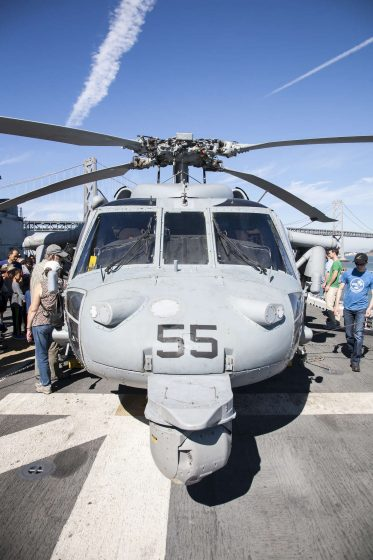 Blake Randall (right) walks around a military helicopter during a tour aboard the USS America Monday, October 13, 2014. Martin Bustamante / Xpress.