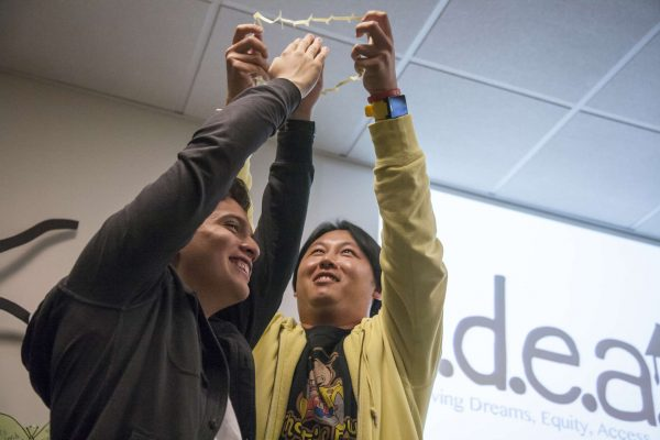 Danny Chau (right) fits Diego Castro (left) through a cut up index card to demonstrate the idea of possibilities during an IDEAS meeting in the library Wednesday, Nov. 12, 2014. Martin Bustamante/Xpress.