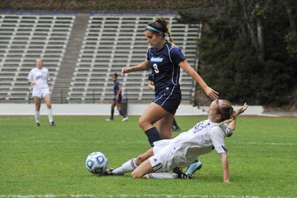 SF State Gators player Autumn Fox, #4, slides to clear the ball away from Sonoma State Seawolves player Cecilia Sifuentes #9, at Cox Stadium Thursday, Oct. 30, 2014. Sara Gobets/Xpress,