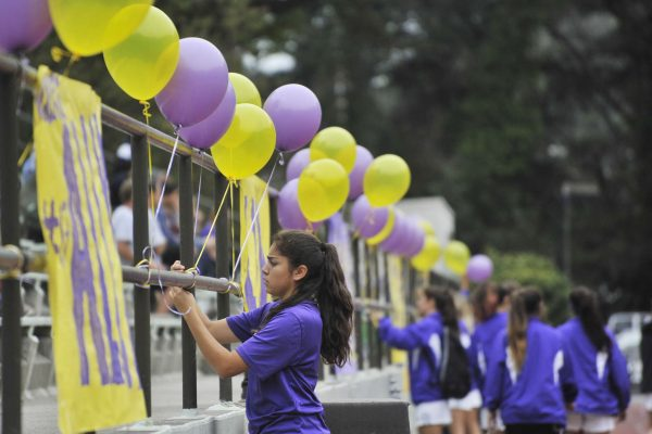 SF State Gators player Karla Uribe and the rest of the women's soccer team decorate the railing at Cox Stadium to honor their graduating players on their last game Thursday, Oct. 30, 2014. Sara Gobets/Xpress.