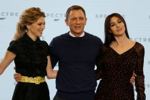 """Actors Lea Seydoux, Daniel Craig and Monica Bellucci pose on stage during an event to mark the start of production for the new James Bond film """"Spectre"""", at Pinewood Studios"""
