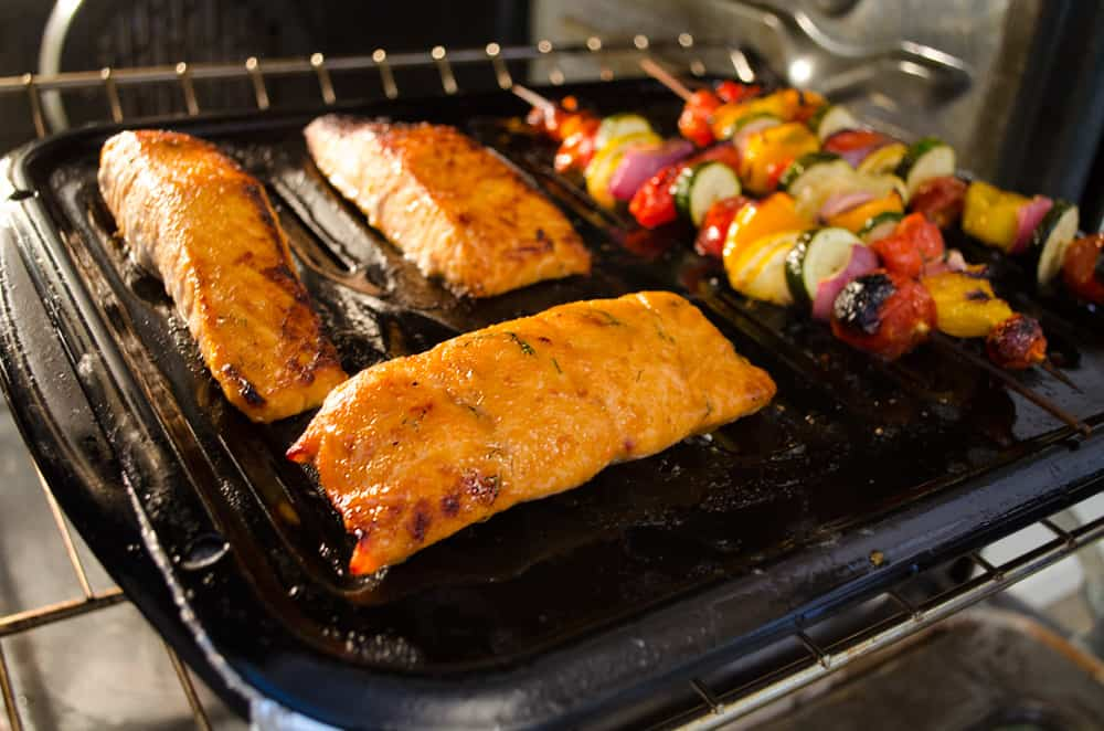 Salmon and veggie skewers on a broiler pan