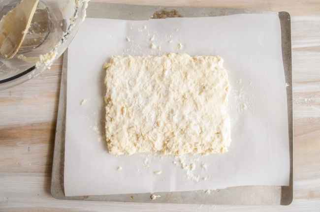 Biscuit dough shaped in a rectangle on a baking sheet for Quick Fluffy Coconut Biscuits.