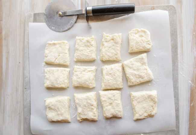Biscuit dough for Quick Fluffy Coconut Biscuits cut into squares on a baking sheet ready for the oven.