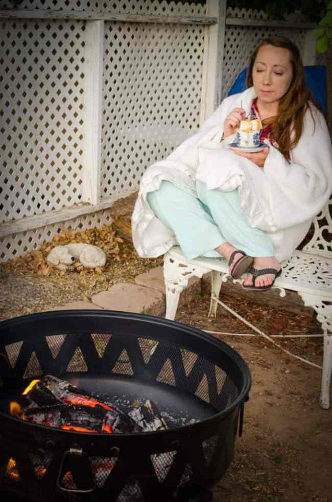 Emily enjoying her S'mores Cake with Roasted Marshmallows by the backyard campfire.