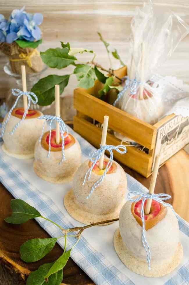 The Best Caramel Apple Recipe displayed with several apples lined in a row tied with blue bows.