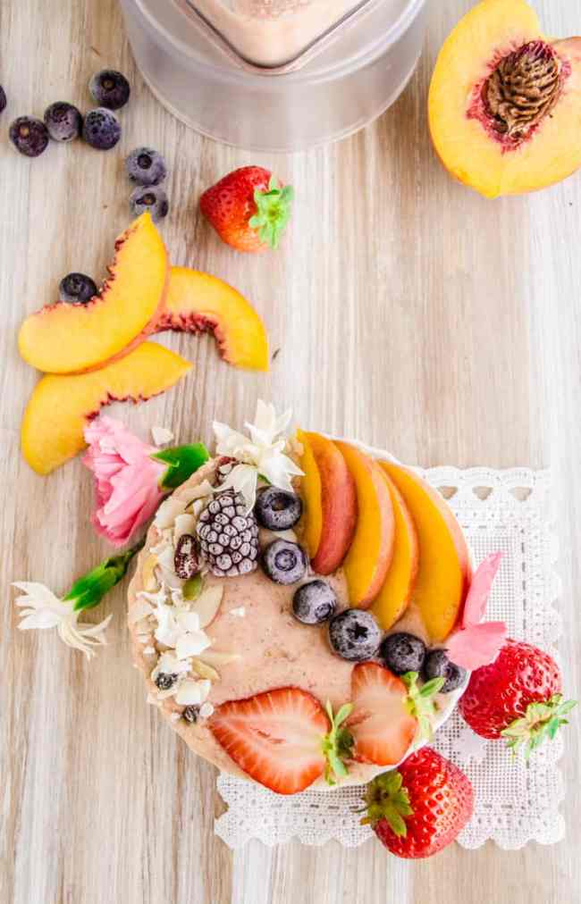 Strawberry Peach Coconut Smoothie Bowl surrounded by fresh strawberries peaches and flowers.