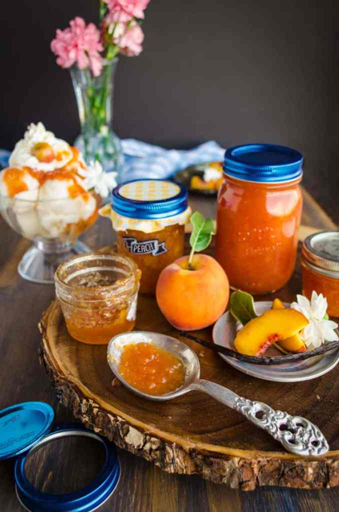 Homemade Vanilla Bean Peach Jam sits on a spoon surrounded with jars of jam and fresh peaches.