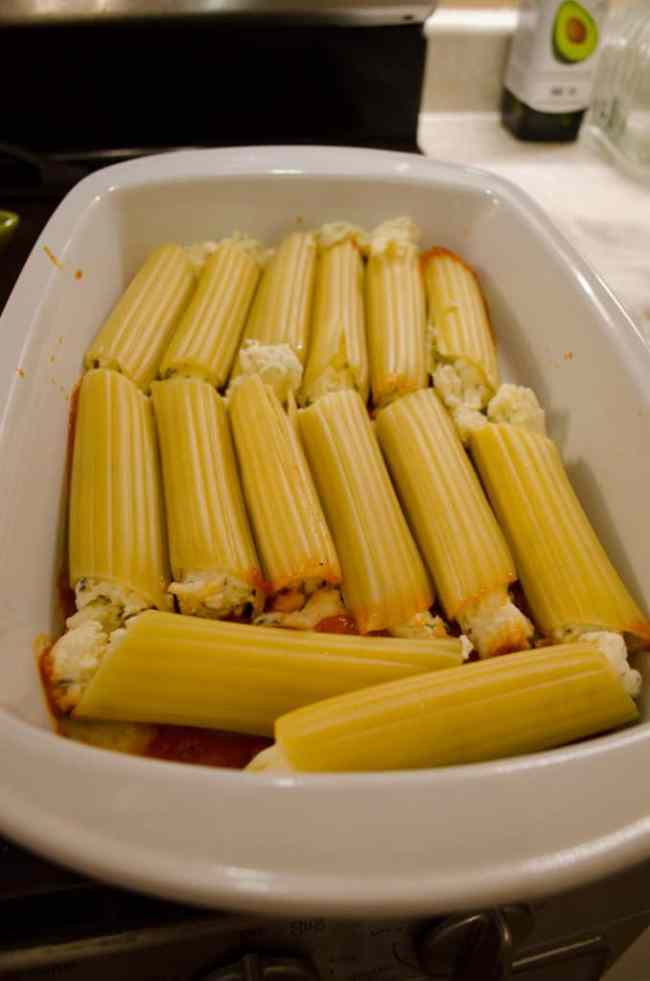 A baking dish is filled with a layer of Meatless Monday Cheese Stuffed Manicotti waiting to be smothered in marinara sauce and cheese.