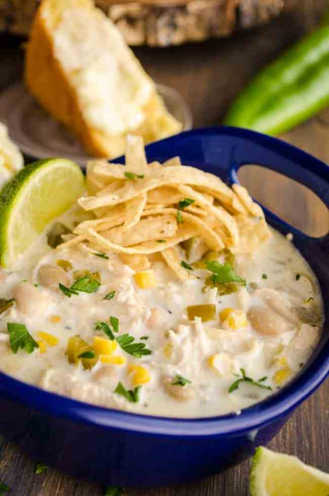 A blue ceramic bowl of Creamy White Chicken Chili is garnished with tortilla strips, a lime wedge, and chopped cilantro.
