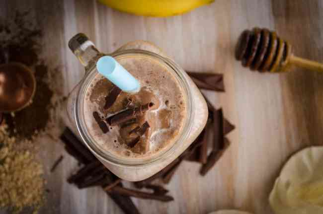 Closeup view of a Peanut Butter Chocolate Banana Smoothie topped with chocolate curls and a blue straw.
