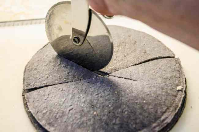 Blue corn tortillas are cut by a pizza cutter into wedges to make Crispy Baked Southwestern Tortilla Chips - The Goldilocks Kitchen