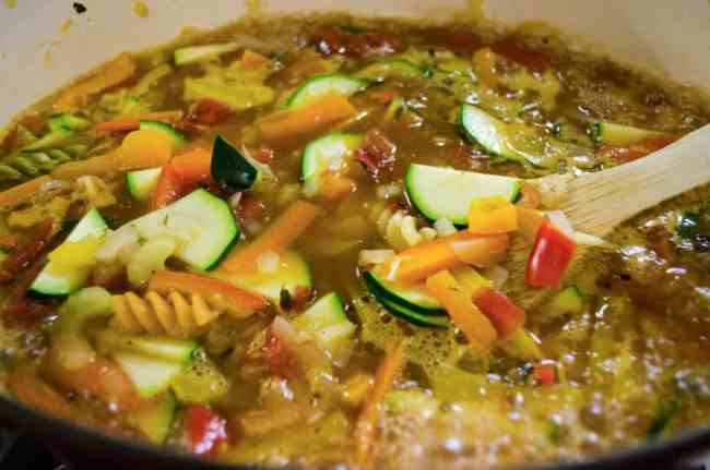 Vegetables, Rotini Pasta and sliced zucchini cook in Meatless Monday Vegetable Rotini Soup.