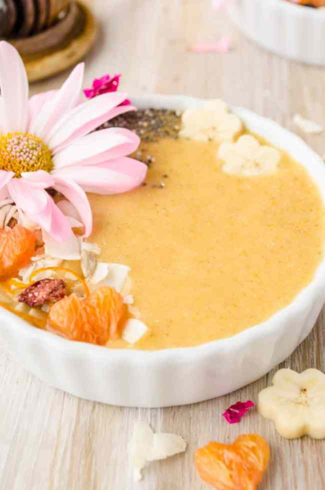A closeup of a Cold Buster Smoothie Bowl topped with fresh banana, orange, chia seeds and coconut Muesli - The Goldilocks Kitchen