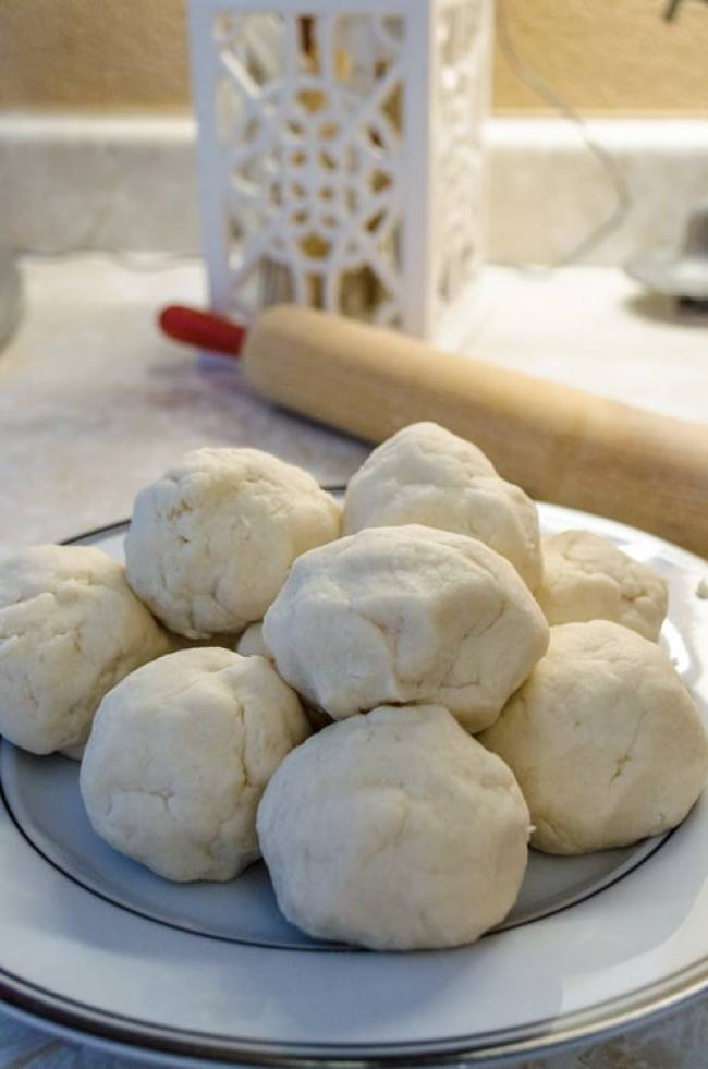 Balls of dough for Norwegian Lefse sit on a plate with a rolling pin in the background - The Goldilocks Kitchen