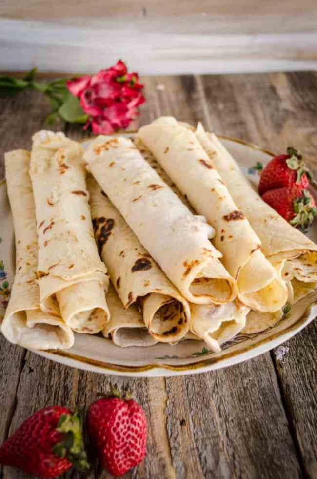 A plate filled with rolled Norwegian Lefse sits with a few strawberries and some red flowers. - The Goldilocks Kitchen
