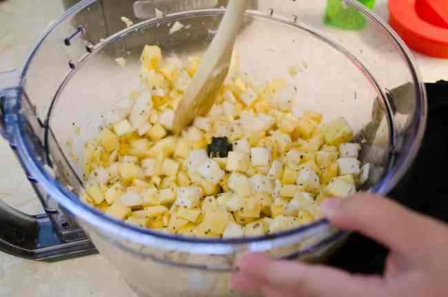 Parsnips, Turnips, and Rutabaga are chopped in a food processor and mixed with olive oil and seasonings for Pesto Pasta with Roasted Root Veggies - The Goldilocks Kitchen