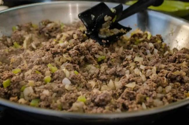 Hamburger, onion, green chile, cumin and chili powder cook in a skillet to make 30 Minute Chili Mac - The Goldilocks Kitchen