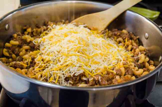 Shredded Mexican cheese blend is added to the beef-macaroni mixture in a skillet to make 30 Minute Chili Mac - The Goldilocks Kitchen