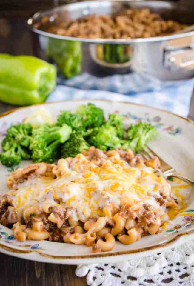 A serving of 30 Minute Chili Mac smothered in cheese sits on a plate with steamed lemon broccoli - The Goldilocks Kitchen