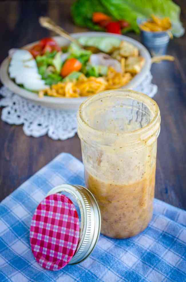 A glass mason jar with Ten Dollar Dressing in it sits in front of a chef's salad. - The Goldilocks Kitchen